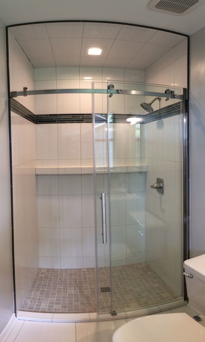 White tile shower with sliding glass door and full wall shelf