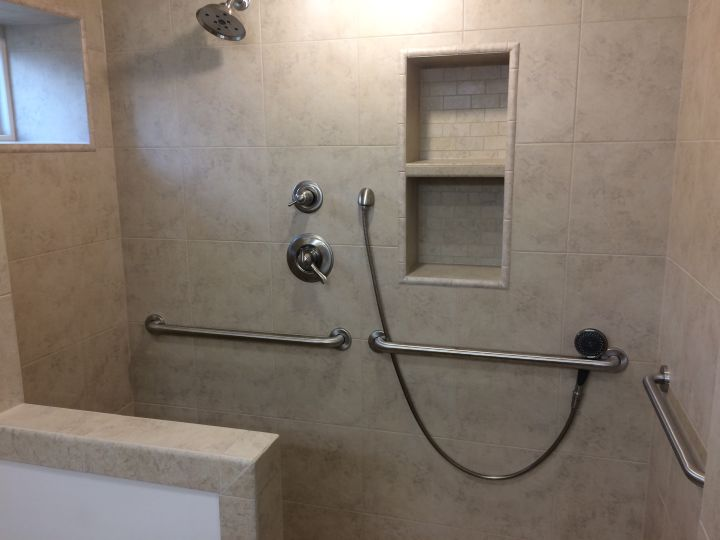 Nickel faucet trim on beige tile shower with recessed niche and window and handicap grab bars