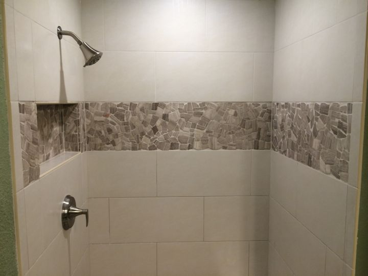 Random stone accent tile on rectangle tile shower
