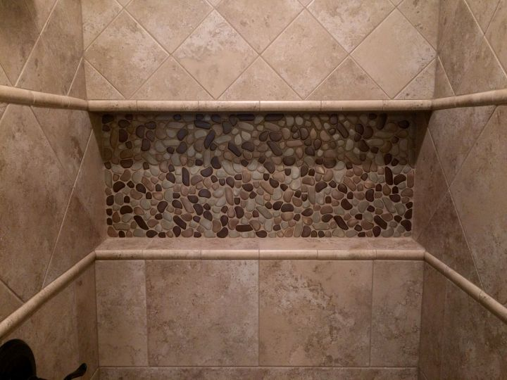 Recessed shampoo shelf that spans the full width of tile shower
