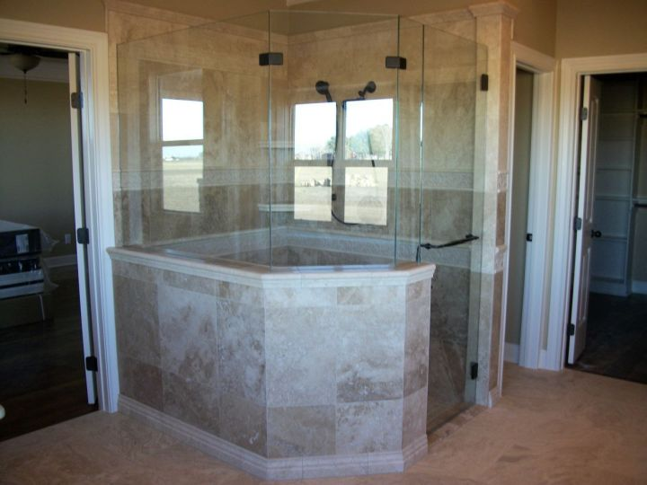 travertine tile shower with frameless glass enclosure