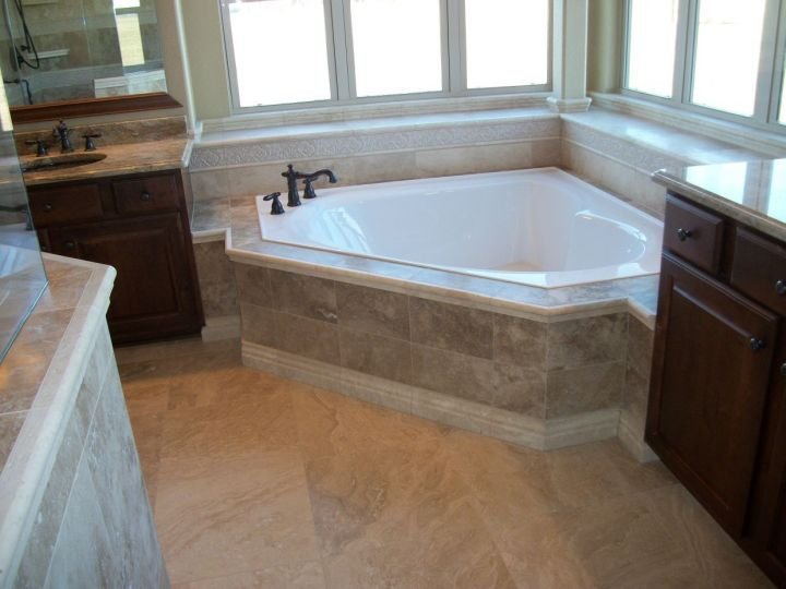 travertine tile on a garden corner tub with base, listello and window seat