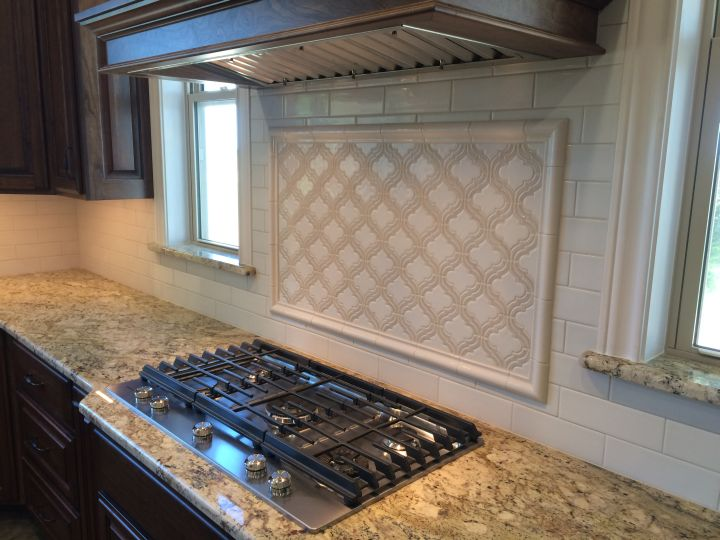 Long subway tile on kitchen backsplash with framed arabesque tile over cooktop