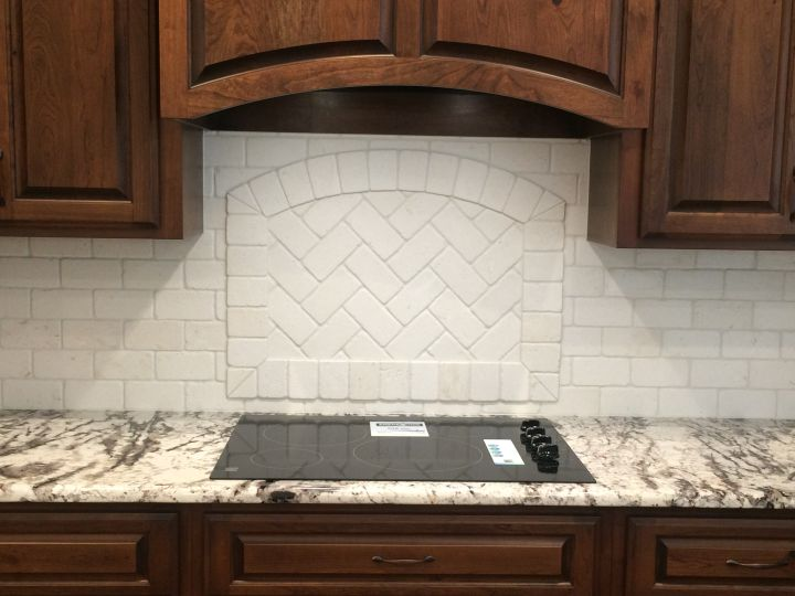 Framed tile accent behind cooktop with herringbone pattern