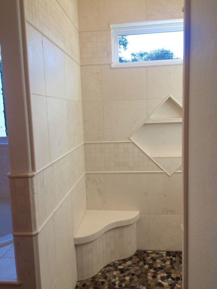 Entrance into white travertine tile shower shows the seat, niche and window